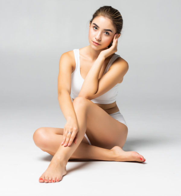 Wellness and beauty concept, beautiful slim woman in white underwear sitting on white floor